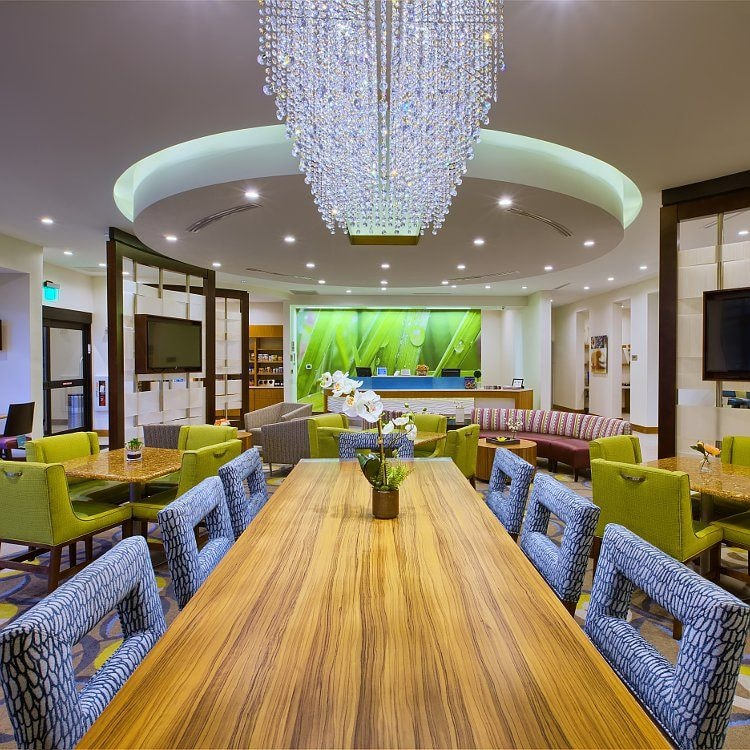 Dramatic hotel lounge with seating, communal table and chandelier