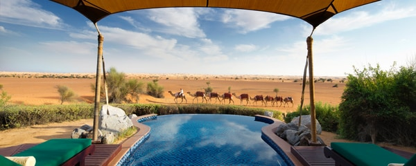 Canopied pool with camel caravan in the distance