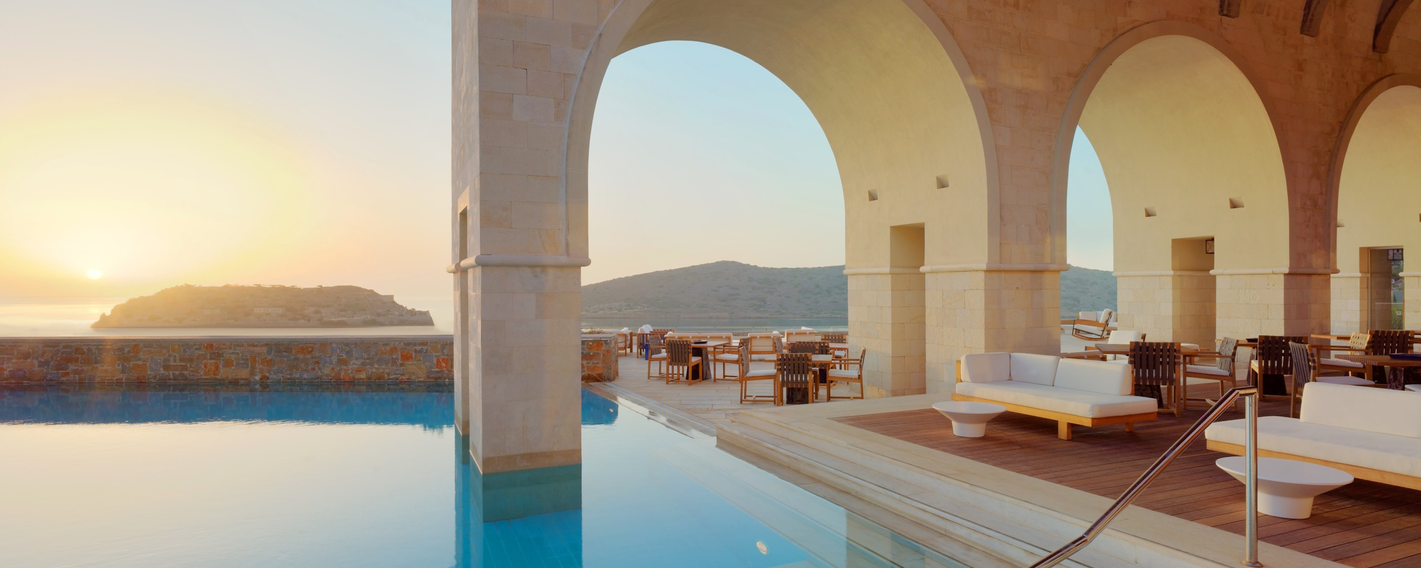 Outdoors lounge with stone archways overlooking the pool