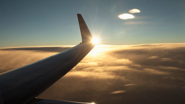 The wing of a plane above the clouds at sunset