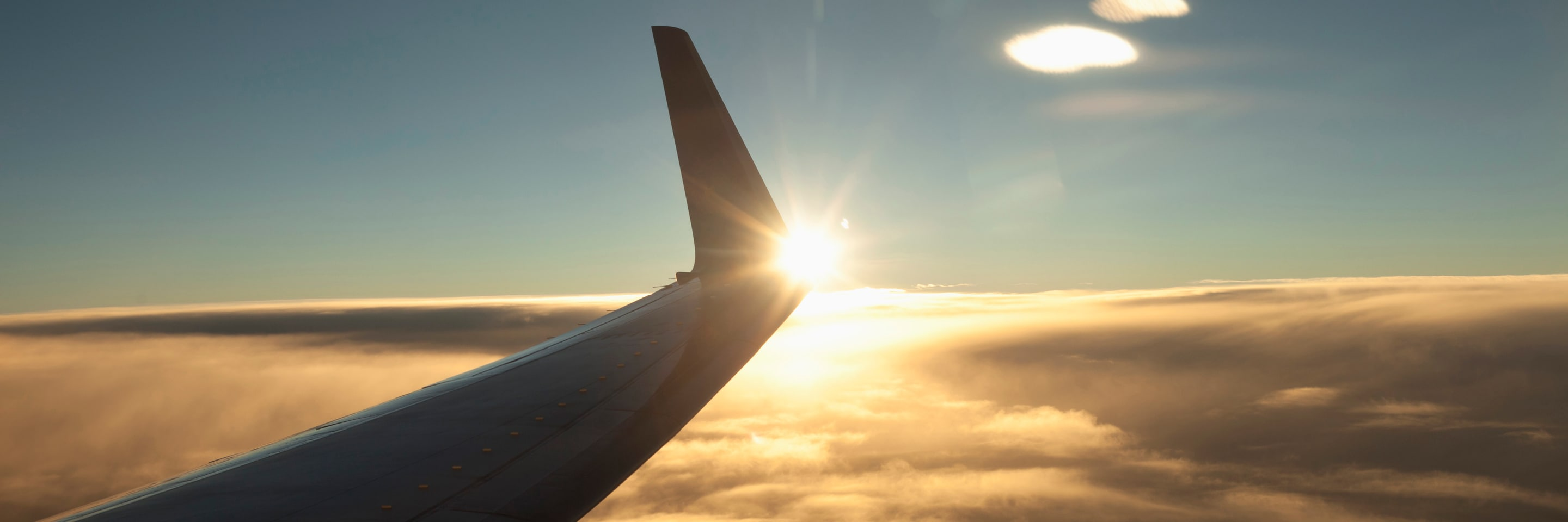 Airplane wing above clouds at sunset