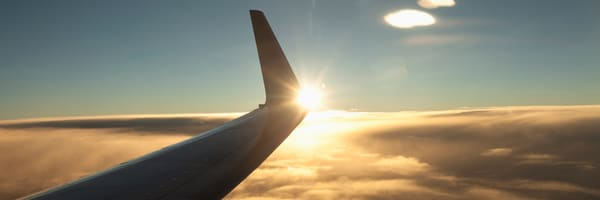 Aeroplane wing above clouds at sunset