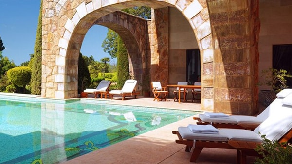 Outdoors lounge with stone archways overooking the pool