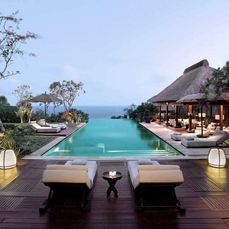 Langer, rechteckiger Infinity-Pool mit Meerblick bei Abenddämmerung, daran angrenzend ein strohgedeckter Lounge-Bereich