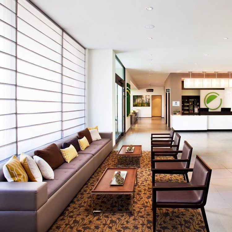 Sleek hotel lounge with chairs, long leather sofa and coffee tables