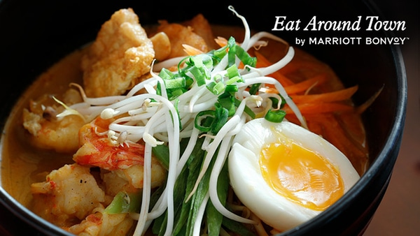 A takeout dinner. Eat Around Town by Marriott Bonvoy logo.