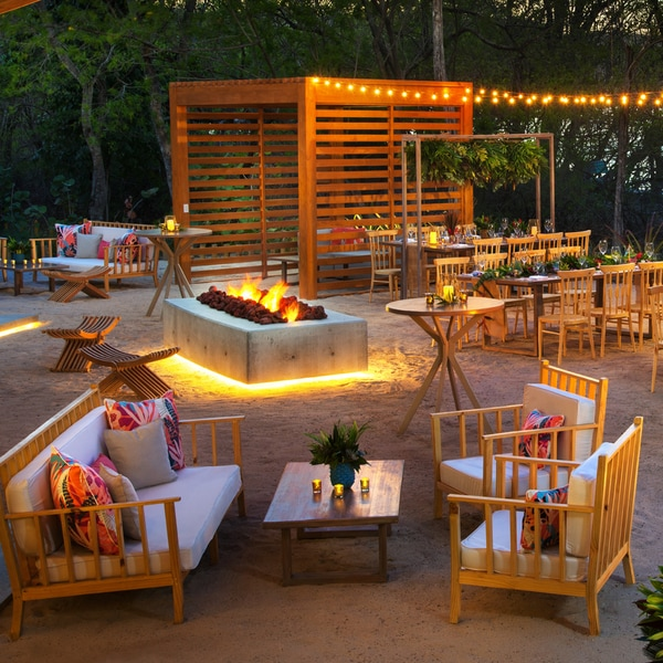 Outdoor tropical dining space surrounded by trees