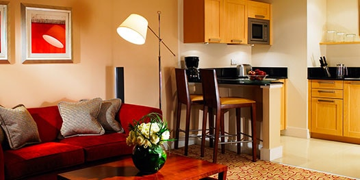 Suite with sofa, table, lamp and full kitchen