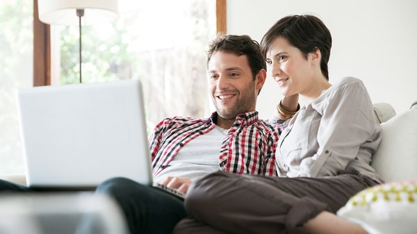 Couple sitting on the sofa with laptop