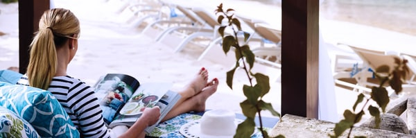 Woman reclining in a beach chair and reading a magazine
