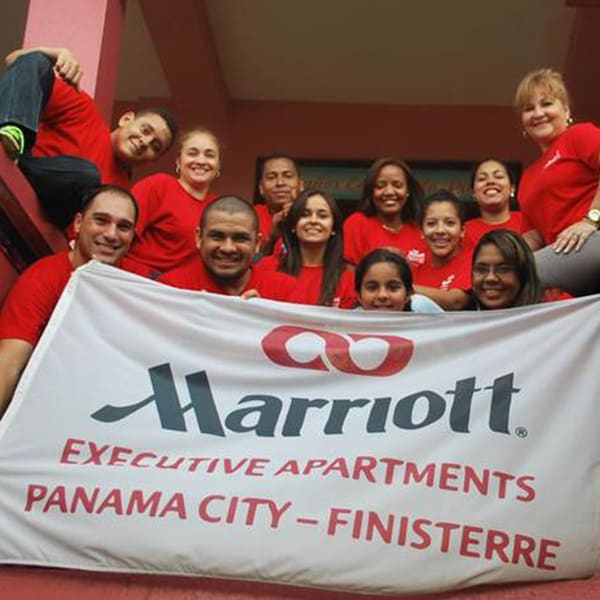 Group of Marriott associates holding a company banner