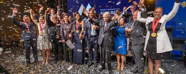 Bill Marriott with 2019 Awards of Excellence winners on stage