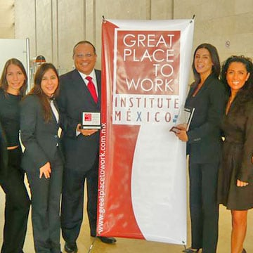 "Five associates stand by a ""Great Places to Work"" banner"