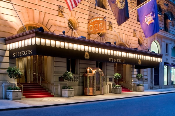 The dramatically lit front entrance to an elegant St. Regis hotel.