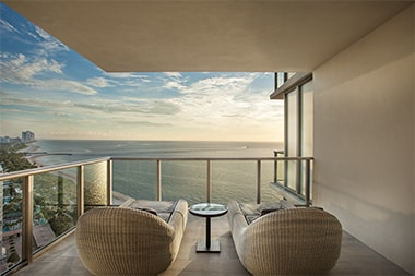 Two sunloungers on a welcoming corner balcony, facing out to sea as the sun sets.