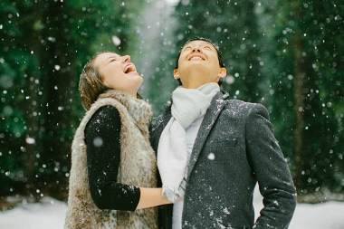 A man and woman in winter clothes look happily to the sky as the snow falls in the forest.