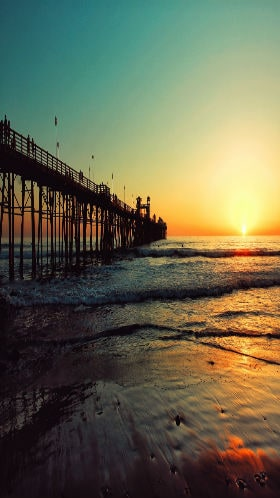 The sun sets over waves lapping on a California beach with a wooden pier.