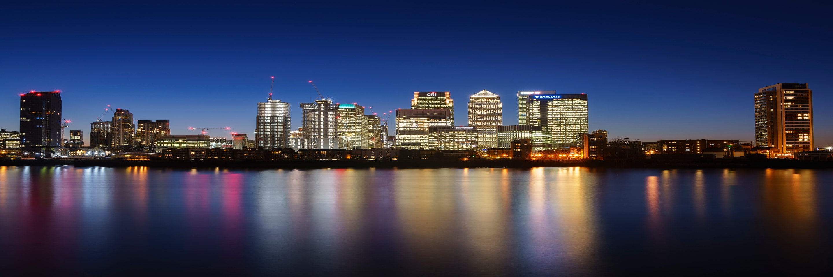East London skyline at night, reflected in the River Thames.