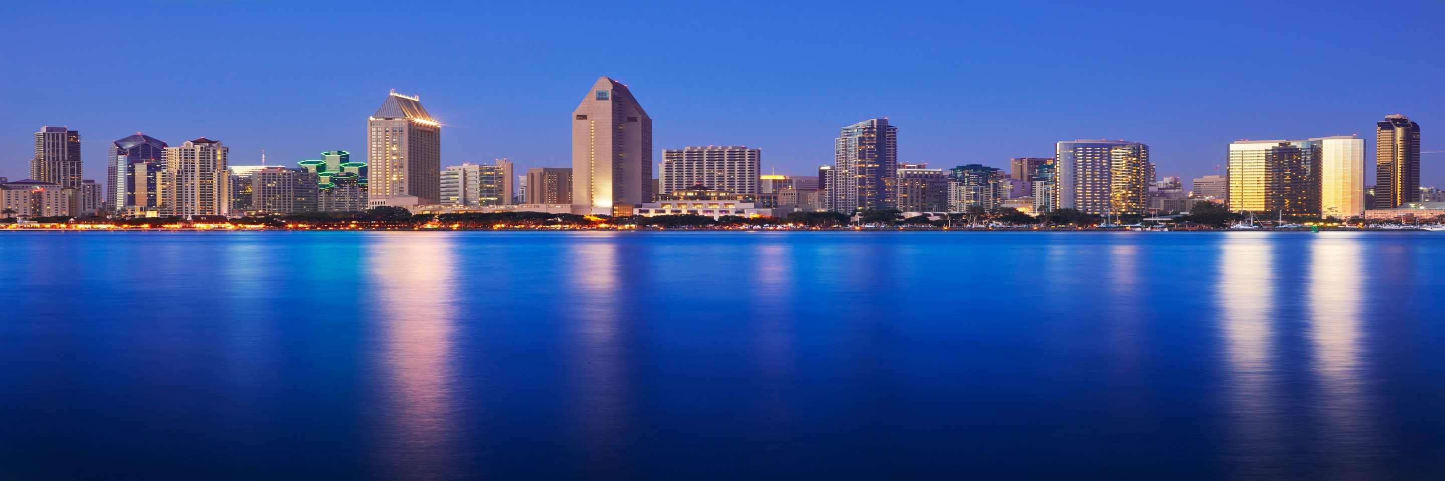 An evening view of San Diego harbor, with lights reflected in the water.