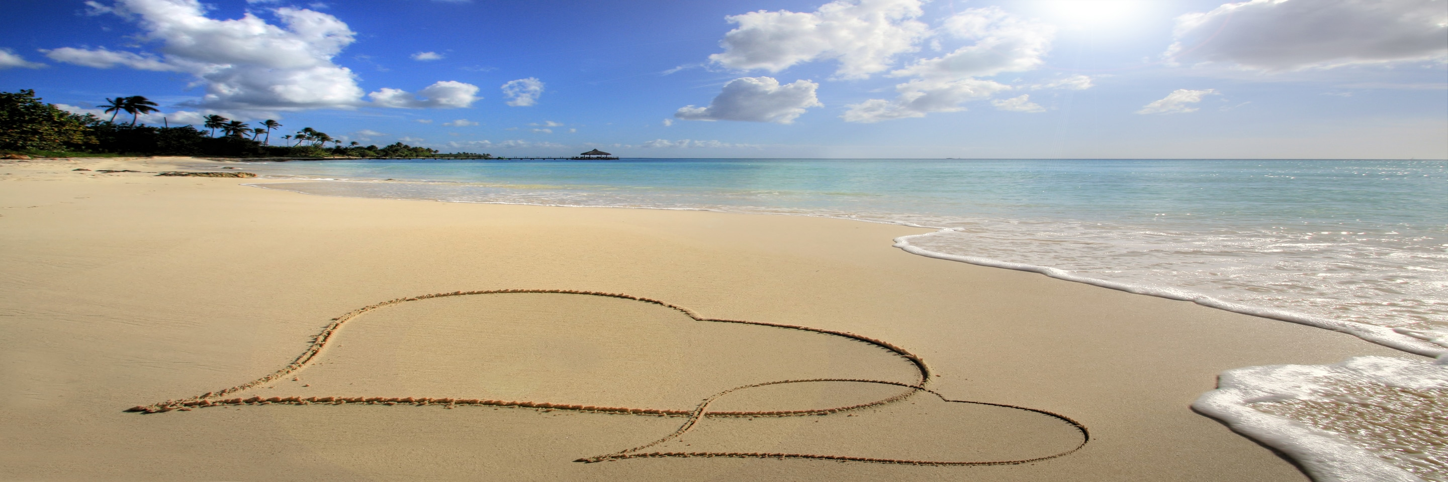Two hearts drawn in the sand, on a deserted tropical beach with lapping waves.