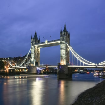 Tower Bridge over the Thames River in London, UK, lit up at twilight
