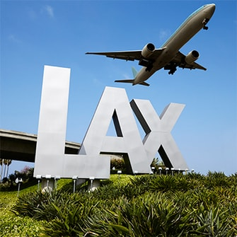 Airplane flying over the LAX sign at Los Angeles Airport