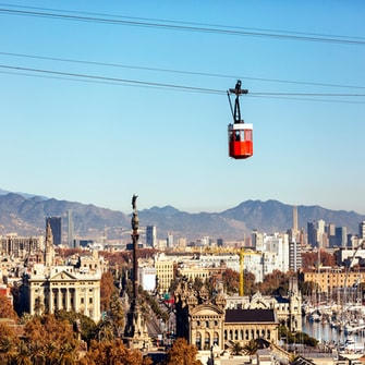 Red cable car over the city of Barcelona in the hazy sunshine.