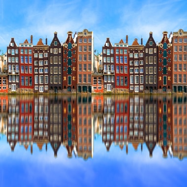 Tall colourful buildings lining the river in Amsterdam.