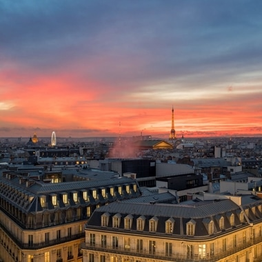 Paris skyline bathed in pink light at dusk, with the Eiffel Tower in the distance.