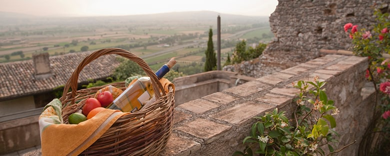 Picnic basket with wine, on a cobbled stone wall, with a view of the countryside.