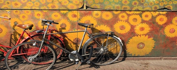 Bikes leaning on a wall painted with sunflowers in Amsterdam.