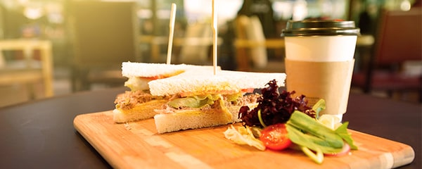 A sandwich on a wooden board, with salad and a takeout coffee.