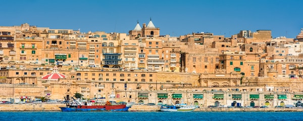 The harbour in Valletta, Malta, busy with boats and with the historic city in the background.