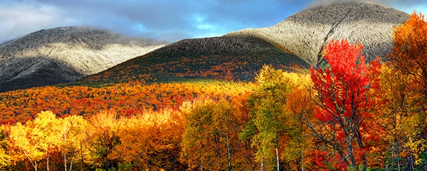 Fall foliage and snowy mountain tops on New Hampshire's White Mountains.