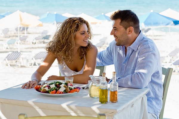 Man and woman sitting at table on the beach