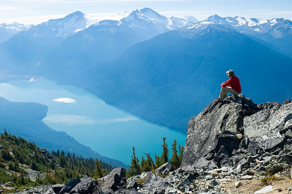 Man sitting on cliff overlooking lake, forest and mountains