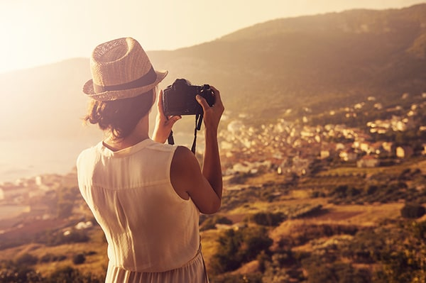 Woman taking photo with camera of village in a valley