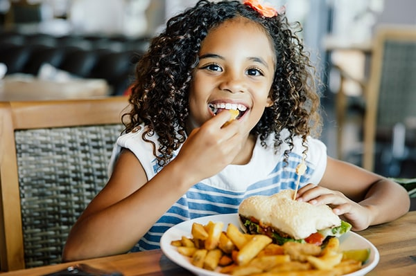 Young girl eating meal at a table