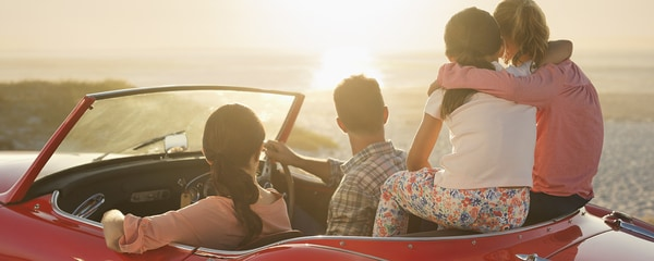 Family of four in a red convertible enjoying the sunset