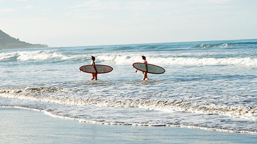 Two people walking into the ocean with surf boards
