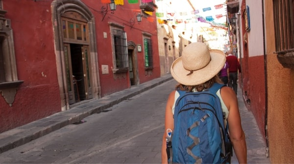 Woman with backpack walking down a narrow street with festive flags