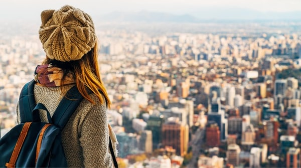 A woman with a backpack looking at the sprawling city below