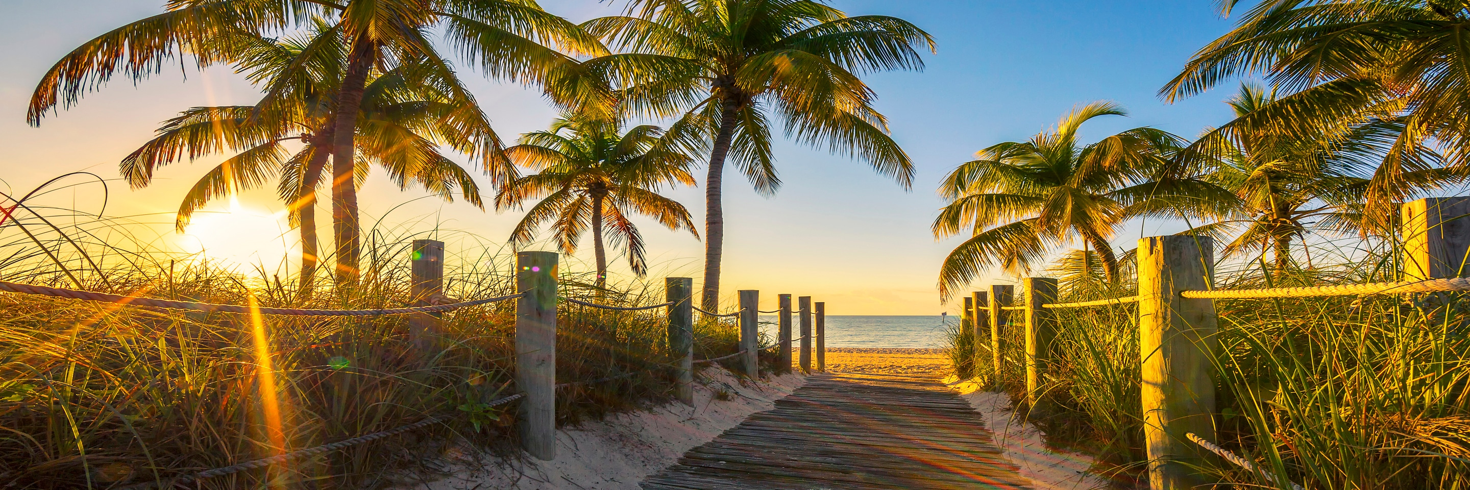 A wooden walkway down to a sandy beach at Key West, Florida at sunrise.