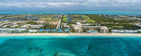 Aerial view of blue waters lining the ocean front hotels in the Cayman Islands.