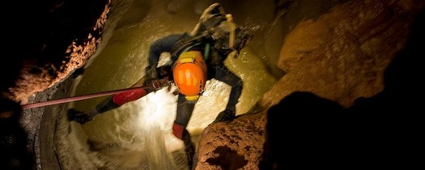 A person dropping into an Alabama cave to explore.