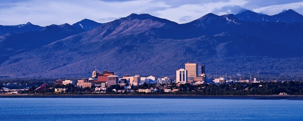 Anchorage's skyline surrounded by mountains.