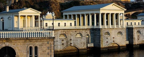 Full view of the Philadelphia art museum along the water in the afternoon sunlight.
