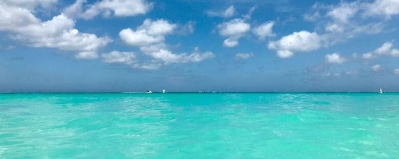 Emerald waters under white clouds in Aruba.