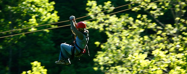 Focused view of a woman riding a zip line through the forest near Asheville, North Carolina.