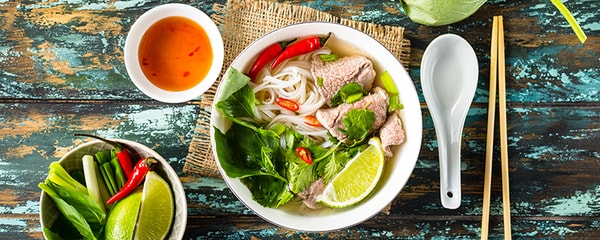 Vietnamese soup pho bo in a white bowl on a colorful wooden table near Austin.